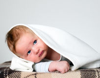 Baby boy holds raised head with blanket over head. Baby boy is holding raised head, happy and amazed child Royalty Free Stock Photos
