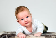 Baby boy holds raised head Royalty Free Stock Images