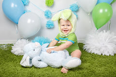Baby boy in holiday Easter bunny rabbit costume with large ears,  dressed in green clothes onesie, sitting on  rug Royalty Free Stock Images