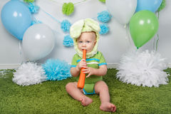 Baby boy in holiday Easter bunny rabbit costume with large ears,  dressed in green clothes onesie, sitting on  rug Royalty Free Stock Image
