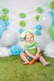 Baby boy in holiday Easter bunny rabbit costume with large ears,  dressed in green clothes onesie, sitting on  rug Stock Photography