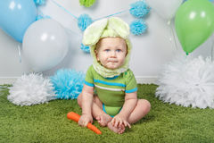 Baby boy in holiday Easter bunny rabbit costume with large ears,  dressed in green clothes onesie, sitting on  rug Stock Photo