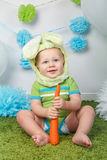 Baby boy in holiday Easter bunny rabbit costume with large ears,  dressed in green clothes onesie, sitting on  rug Royalty Free Stock Photography