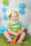 Baby boy in holiday Easter bunny rabbit costume with large ears,  dressed in green clothes onesie, sitting on  rug Royalty Free Stock Photos