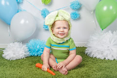 Baby boy in holiday Easter bunny rabbit costume with large ears,  dressed in green clothes onesie, sitting on  rug Stock Image
