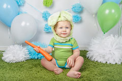 Baby boy in holiday Easter bunny rabbit costume with large ears,  dressed in green clothes onesie, sitting on  rug Stock Photos