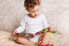 Baby boy at home reading Stock Image