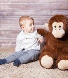 Baby boy with huge monkey toy Stock Photo