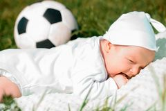 Baby boy infant fun photoshoot soccer football concept big smile having fun playing laughing laying on white furry round through s. Quare composition wearing hat Stock Photography