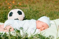 Baby boy infant fun photoshoot soccer football concept big smile having fun playing laughing laying on white furry round through s. Quare composition wearing hat Royalty Free Stock Photos