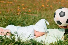 Baby boy infant fun photoshoot soccer football concept big smile having fun playing laughing laying on white furry round through s. Quare composition wearing hat Royalty Free Stock Photo