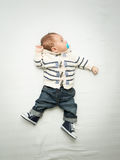 Baby boy in jeans holding soother lying on bed Royalty Free Stock Image