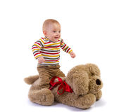 Baby boy jumps on plush dog Royalty Free Stock Images