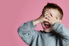 Baby boy kid covering close his eyes with hands and palms screaming laughing  over pink royalty free stock photos