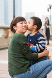 Baby boy kiss his mother on her face. The baby boy is kissing his mother on her face Royalty Free Stock Photos