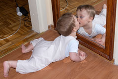 Baby boy kiss in mirror.  Stock Photos