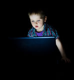 Baby boy laptop. Little kid using laptop by night Royalty Free Stock Images