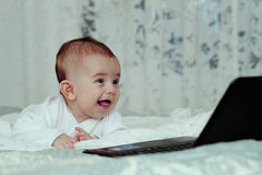 Baby boy with laptop Stock Image