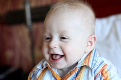 Baby boy laughing. Portrait of cute baby boy laughing indoors stock photos