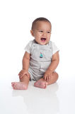 Baby Boy Laughing and Looking off to the Side of Frame. A portrait of a seven month old, hispanic baby boy laughing. He is wearing overalls with a sailboat decal stock photos