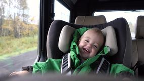 Baby boy laughs in the car in the chair stock footage