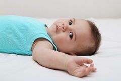 Baby boy laying on bed. White background Royalty Free Stock Photography