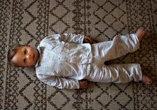 Baby boy laying on carpet in pajama Royalty Free Stock Image