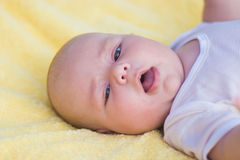 Baby boy laying down. Cute baby boy lying on her belly in a yellow towel Royalty Free Stock Image