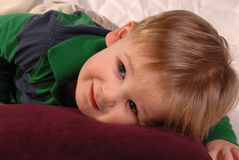 Baby boy laying on a pillow innocent look. Wearing casual cloths on white crinkled background Royalty Free Stock Images