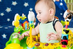 Baby boy learning to walk in funny babywalker. With toys royalty free stock image