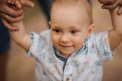 Baby boy learning to walk and making his first steps holding hands of father. Royalty Free Stock Photo