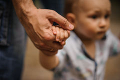 Baby boy learning to walk and making his first steps holding hands of father. stock photography