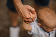 Baby boy learning to walk and making his first steps holding hands of father. stock images