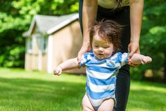 Baby boy learning to walk outside. With the help of his parents stock photography