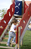 Baby boy learns to climb stairs. Active baby boy learns to climb wooden  slide stairs on the playground Royalty Free Stock Images