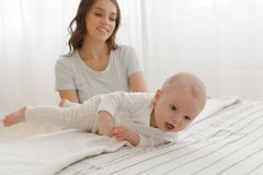 Baby boy learns to roll over on his back on bed. Baby boy learns to roll over on his back happy family. Mother and baby playing and smiling on the bed Royalty Free Stock Image