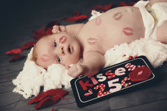 Baby boy with lipstick kisses all over him Stock Photos