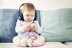 Baby boy listening music at earphones with iphone in hands. Royalty Free Stock Image