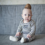Baby boy. Little boy is sitting on a gray couch Royalty Free Stock Photos