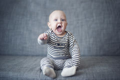 Baby boy. Little boy is sitting on a gray couch Stock Images