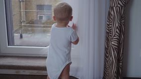 The boy at the window. The baby boy is looking in the big window stock video