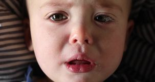 Baby boy looking at camera with sad face close-up. Head portrait of caucasian boy looking at camera with sad face close-up stock video