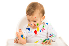 Baby boy looking at colorful paints Royalty Free Stock Photo