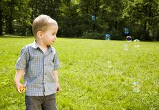 Baby Boy Looking On Soap Bubbles Stock Photos