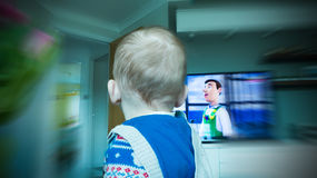 Baby boy looking at TV Stock Photography