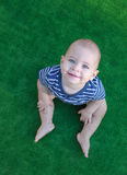 Baby boy looks up. Baby is held hands feet. Stock Images