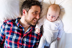 Baby boy lying on bed, next to his father Stock Photography