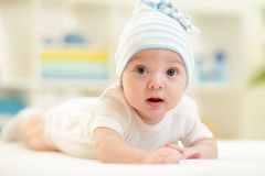 Baby boy lying on bed in nursery Royalty Free Stock Photo