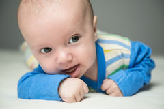 Baby boy lying on the bed. Portrait of 3 month old baby boy wearing blue, green, yellow and white striped jacket lying prone on a bed showing interest and Stock Photos