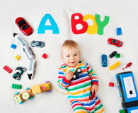 Baby boy lying on the blanket with letters above Royalty Free Stock Photos